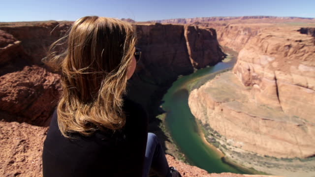 young woman sitting on the edge of the grand canyon - grand canyon stock videos & royalty-free footage