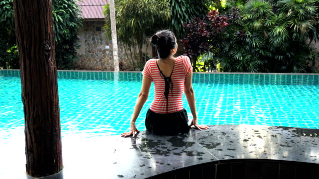 Young woman sitting on the edge of the pool.