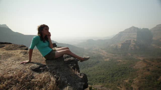 Young woman sitting on the rock and talking on the mobile phone
