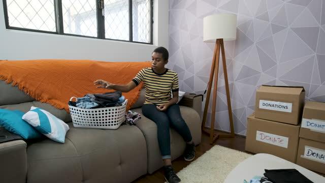 vídeos y material grabado en eventos de stock de mujer joven sentada en el sofá seleccionando ropa para la donación. - sólo mujeres jóvenes