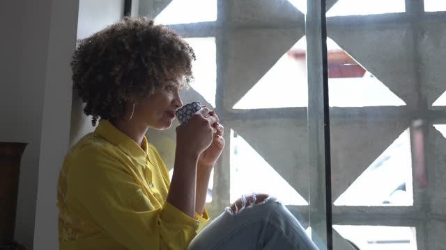 young woman sitting on the window sill looking away and drinking tea at home - looking away stock videos & royalty-free footage