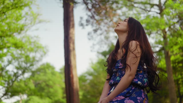 木の幹に座って自然の中にいることを楽しむ若い女性 - barefoot点の映像素材/bロール