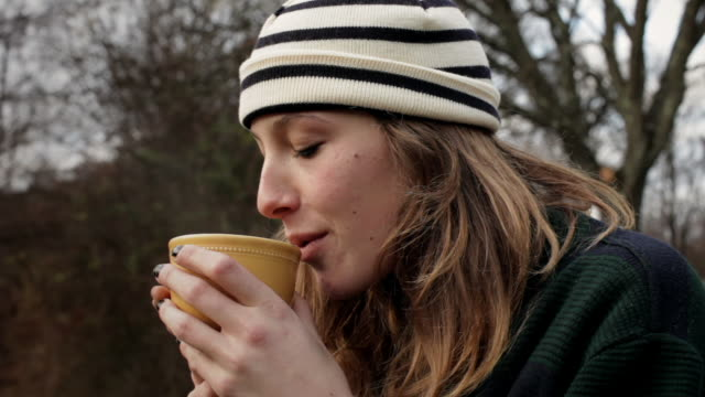 vidéos et rushes de cu young woman sitting outside drinking hot drink / kingston, new york, usa  - hot