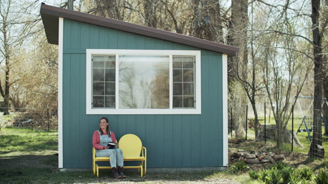 young woman sitting outside her art studio in the woods - drawing activity stock videos & royalty-free footage