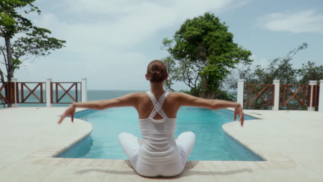 MS RV Young woman sitting poolside and stretching arms above head in yoga position/ Scarborough, Tobago, Trinidad and Tobago