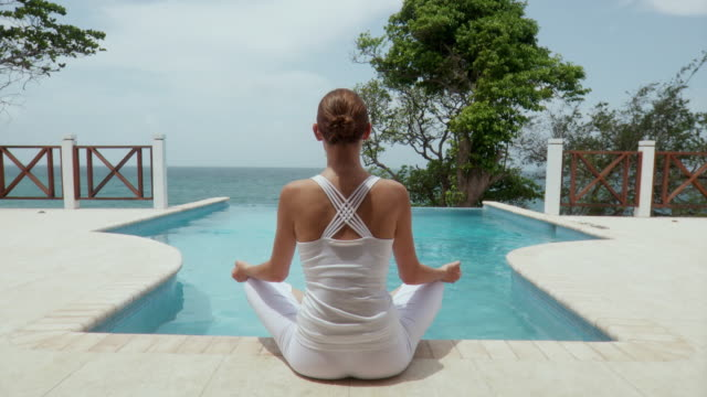MS RV Young woman sitting poolside in yoga position/ Scarborough, Tobago, Trinidad and Tobago