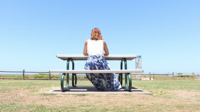 young woman sitting thinking at a picnic seat by the beach - māori people stock videos & royalty-free footage