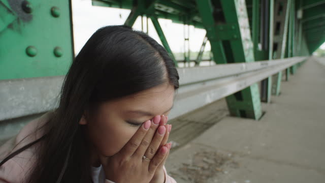 Young woman sitting under bridge. Loneliness. head in hands