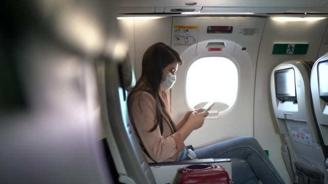 young woman sitting using phone on the aircraft seat wearing face mask - airport stock videos & royalty-free footage