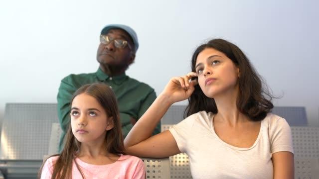 ung kvinna sitter med dotter i väntrummet på sjukhuset - väntrum bildbanksvideor och videomaterial från bakom kulisserna