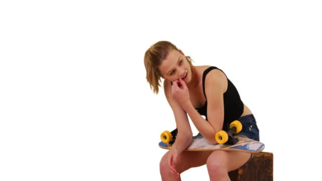 young woman skateboarder sitting on box on white background with copy space - board shorts stock videos and b-roll footage