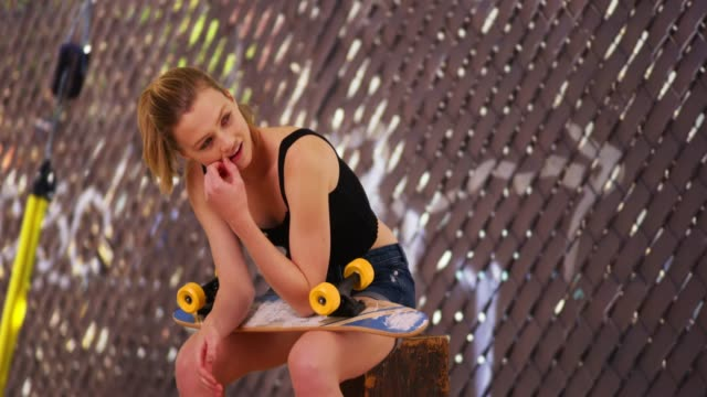 young woman skateboarder sitting on box outside at skate park with short board - board shorts stock videos and b-roll footage