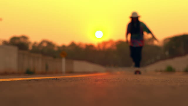 young woman skateboarding at sunset - skateboard stock videos & royalty-free footage
