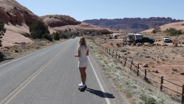 vídeos y material grabado en eventos de stock de joven patina a lo largo del camino del desierto, más allá de las rocas - menos de diez segundos