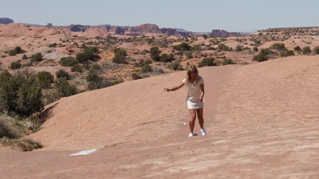 young woman skateboards along slickrock rock slab - moab utah stock videos & royalty-free footage