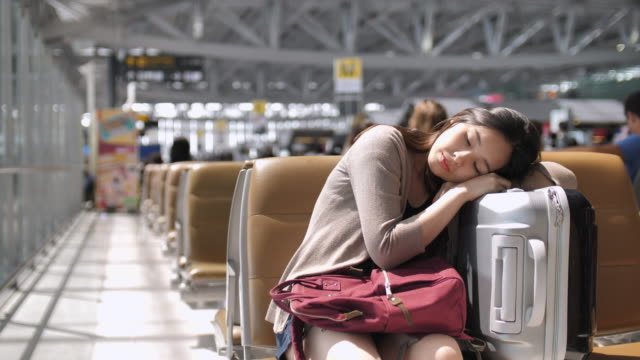 vídeos de stock e filmes b-roll de young woman sleep at the airport waiting for her flight - aviation fatigue