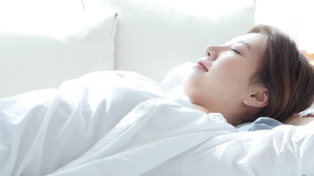 vídeos y material grabado en eventos de stock de a young woman sleeping in bed and enjoying single life in the morning - manos detrás de la cabeza