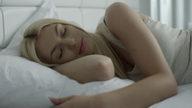 Young woman sleeping in bedroom