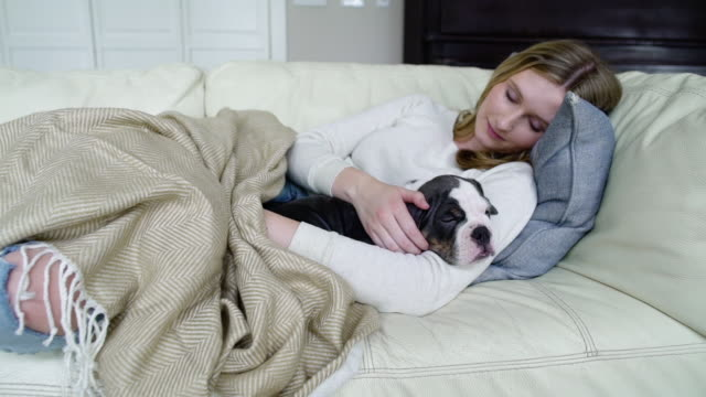 Young woman sleeping on a couch with her puppy