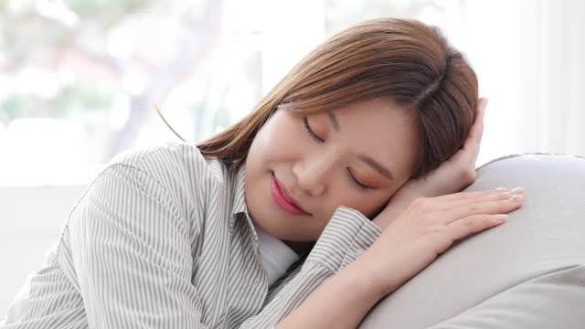 vídeos y material grabado en eventos de stock de a young woman sleeping on sofa comfortably in her living room - manos detrás de la cabeza