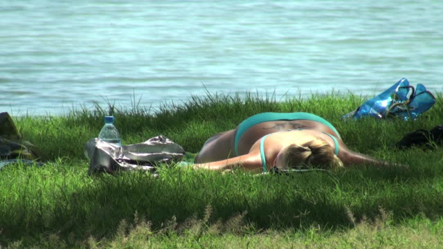 young woman sleeping on the grass near thè sea - grass family stock videos & royalty-free footage
