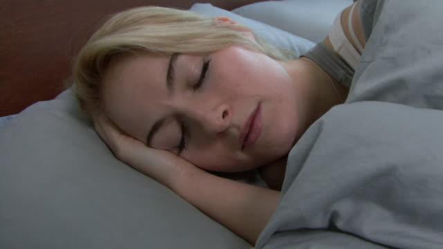 vídeos de stock, filmes e b-roll de young woman sleeping; uk - deitar