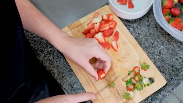 vídeos y material grabado en eventos de stock de joven cortando fresas para producción de mermelada - una mujer de mediana edad solamente
