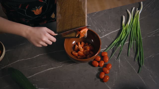 young woman slides tomatoes in bowl showing how to cook salad - sich verschönern stock-videos und b-roll-filmmaterial