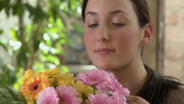 cu young woman smelling bouquet of flowers and then sneezing / berlin, germany - ponytail stock videos & royalty-free footage