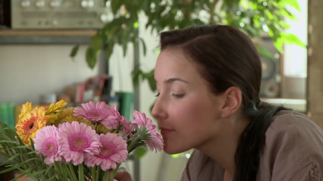 cu young woman smelling bouquet of pink flowers / berlin, germany - 嗅ぐ点の映像素材/bロール