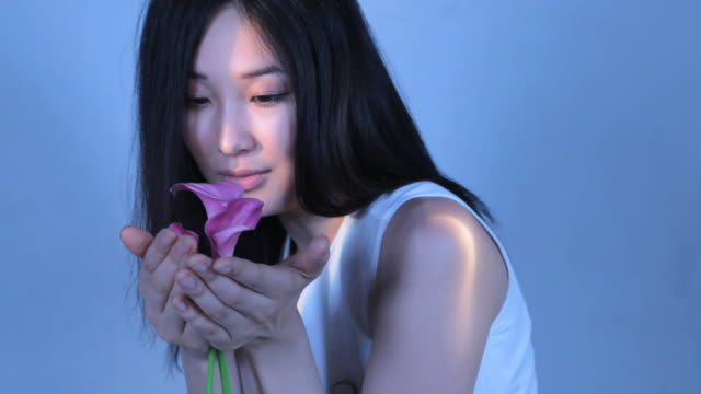 CU ZO Young woman smelling calla lily flowers / New York, New York, USA
