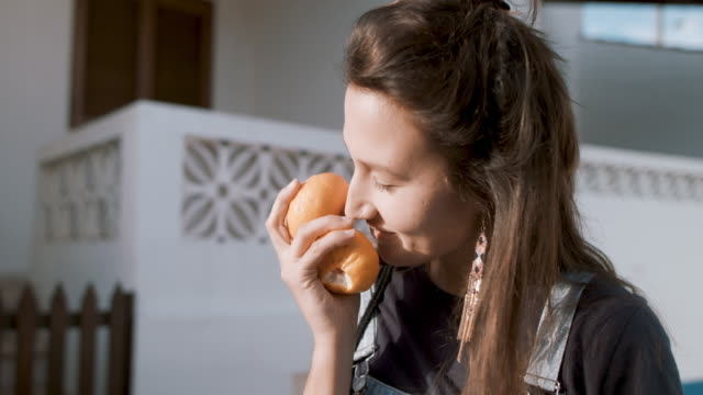 vídeos de stock e filmes b-roll de young woman smelling mandarins in sunshine - laranja