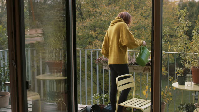 young woman smelling, watering plants on balcony - young women stock-videos und b-roll-filmmaterial