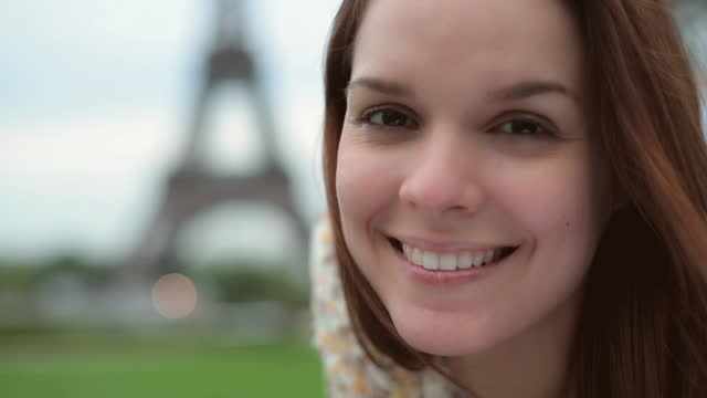 cu. young woman smells flower and smiles at camera with eiffel tower out of focus in background. - frische stock-videos und b-roll-filmmaterial