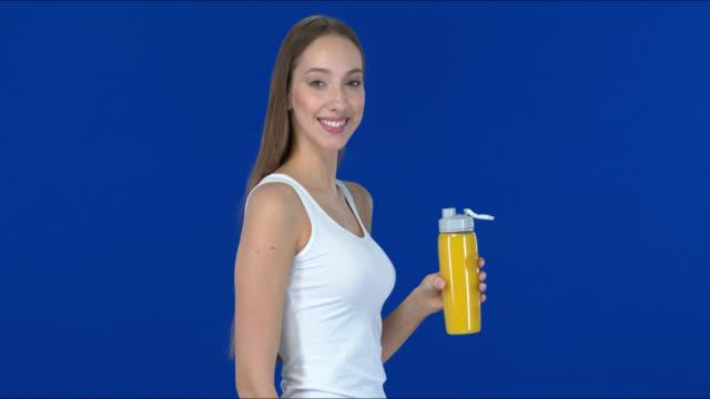 stockvideo's en b-roll-footage met de jonge vrouw glimlacht en drinkt sinaasappelsap van een fles. - natuurlijk haar