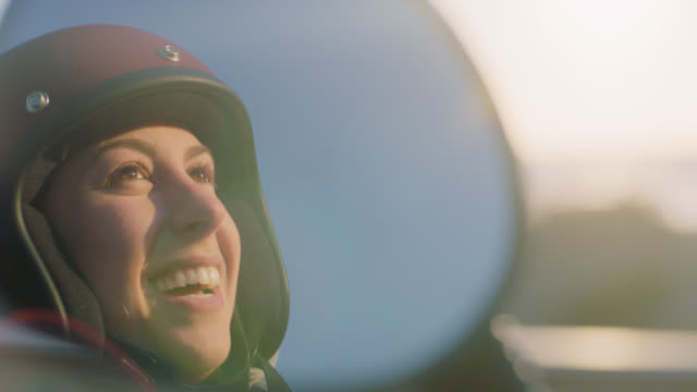 ECU SLO MO. Young woman smiles and laughs reflected in motorcycle side mirror.