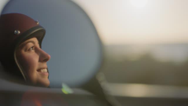 vídeos de stock, filmes e b-roll de cu slo mo. young woman smiles and looks over the ocean reflected in motorcycle side mirror. - capacete esportivo