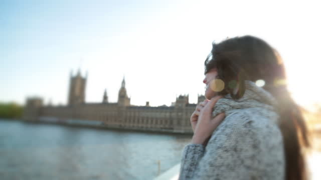 HANDHELD CLOSE UP young woman smiles and flirts with camera with Big Ben and Parliament in background in London