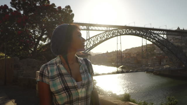 Young woman smiles and walks along river - Porto, Portugal