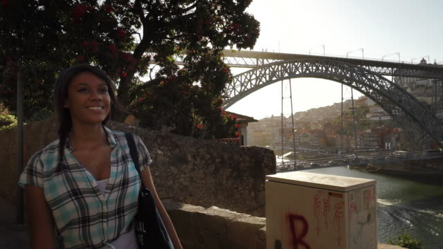young woman smiles and walks along river - porto, portugal - porto district portugal stock videos & royalty-free footage
