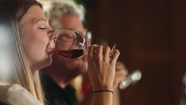 slomo. young woman smiles as she sips a glass of rose-colored wine during a taste-testing event at a winery. - bicchiere da vino video stock e b–roll