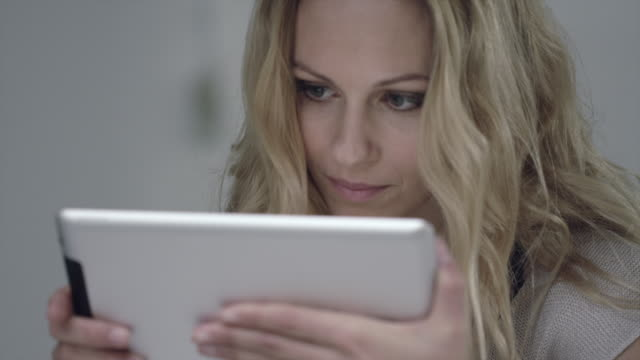 A young woman smiles as she views a digital tablet.