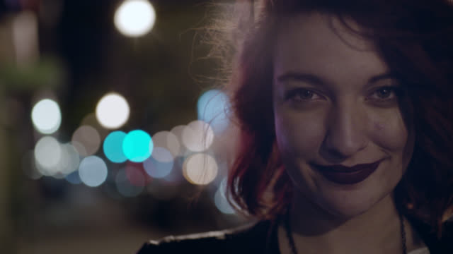 vídeos de stock e filmes b-roll de cu slo mo. young woman smiles at camera and looks down on city sidewalk at night. - cool