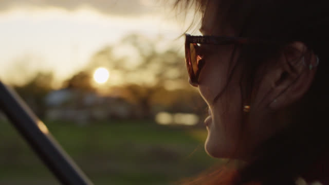 young woman smiles at camera and stares out at setting sun from backseat of classic bronco - auto convertibile video stock e b–roll
