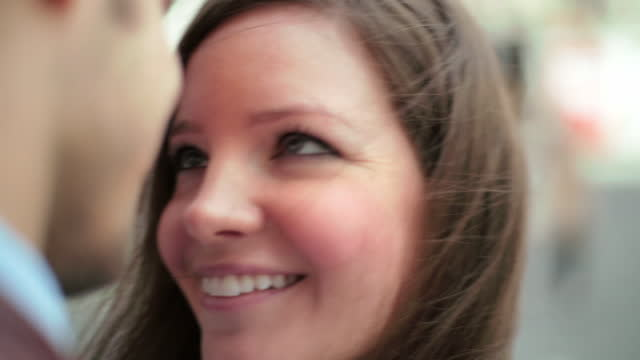 A young woman smiles before embracing her boyfriend.