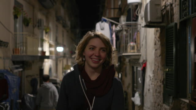 young woman smiles walking at night in naples, italy - vorderansicht stock-videos und b-roll-filmmaterial