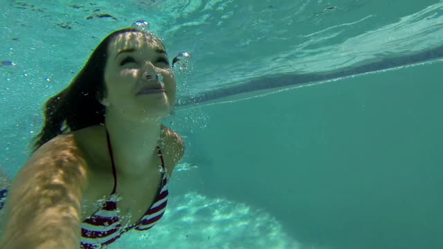 vídeos de stock, filmes e b-roll de sorrisos de mulher jovem enquanto nadava debaixo d'água na piscina do quintal - prendendo a respiração