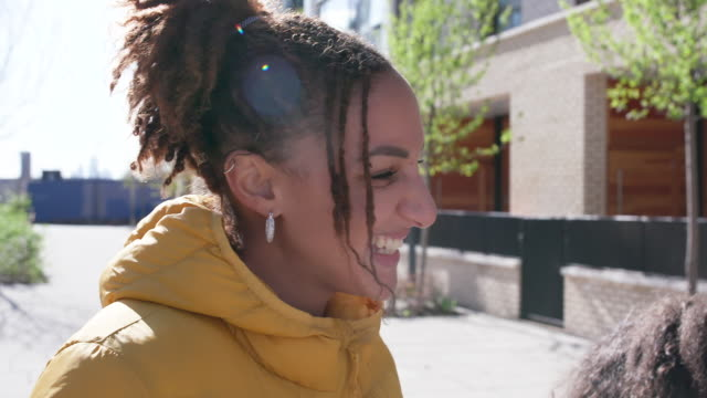 young woman smiling and chatting with friends outside in the sun - social gathering stock videos & royalty-free footage