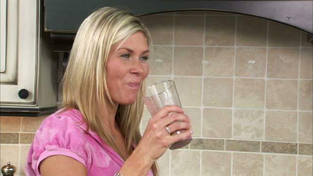 cu young woman smiling and drinking fruit smoothie in kitchen / salt lake city, utah, usa - korta ärmar bildbanksvideor och videomaterial från bakom kulisserna
