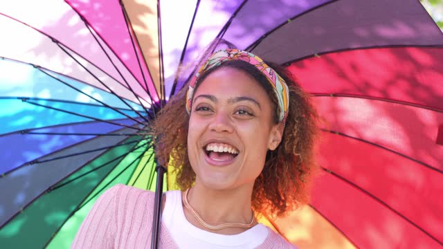 young woman smiling holding colourful umbrella - spectrum stock videos & royalty-free footage